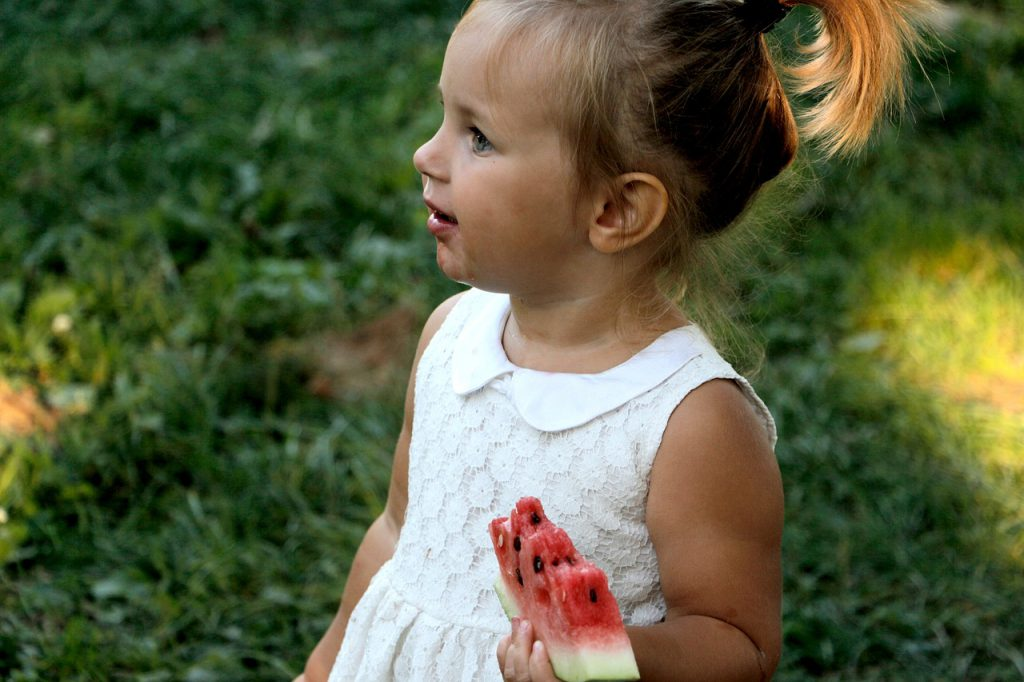 young girl eating watermelon